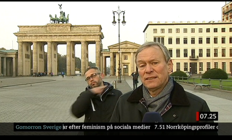 migrant slitting throat behind reporter.png