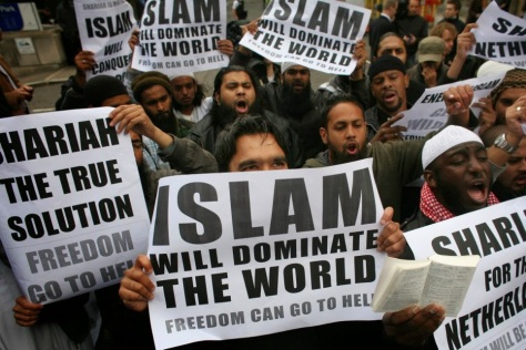 Muslims carrying banners declaring 'Islam will dominate the world' protest at the visit of Mr Wilders to the UK